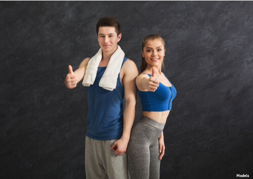 Man & Woman giving a thumbs up after a workout