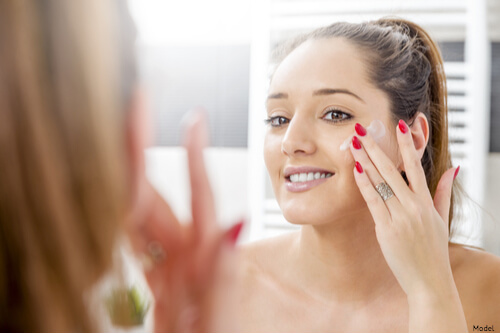Woman putting on medical-grade skincare products