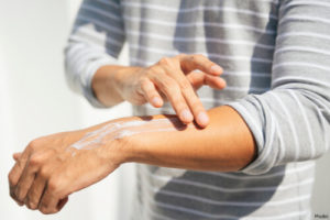 person applying lotion to their arm