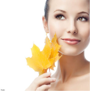 Woman holding a leaf to her face